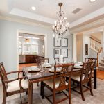 Formal dining room with crystal chandelier and Italian-style columns.