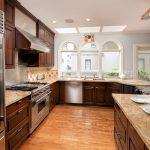 Luxe kitchen with granite countertops, ceramic backsplash, oak hardwood floors, skylights, an eating and serving bar.